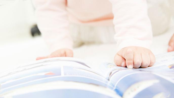 図鑑を指さす幼児