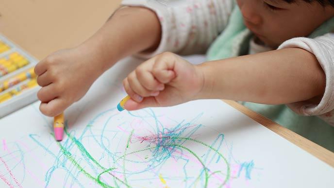 クレヨンでお絵描きする幼児