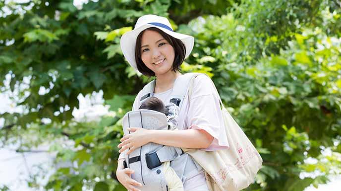 赤ちゃんを抱っこして公園を散歩する女性