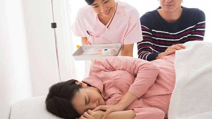 病床で陣痛が始まる妊婦