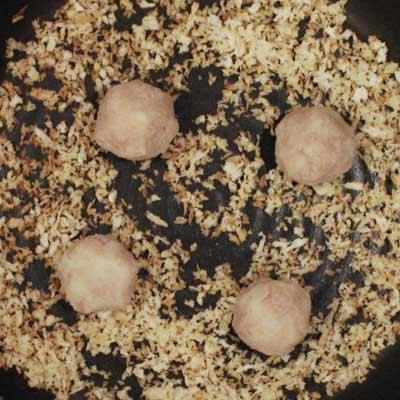 フライパンの中の炒ったパン粉のうえに置かれた4つのコロッケ生地
