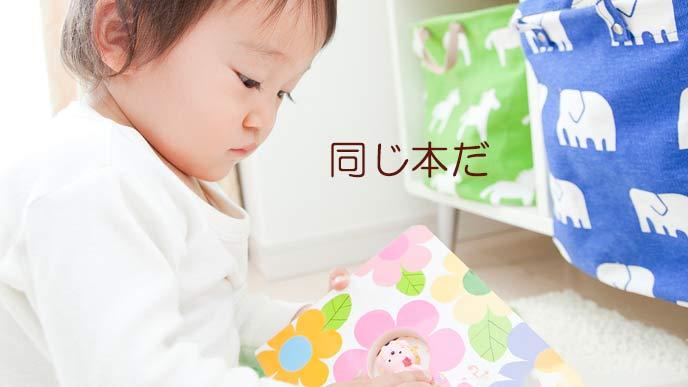 絵本を開いて見つめる赤ちゃん