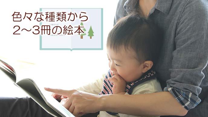 赤ちゃんが見る絵本を指さす母親