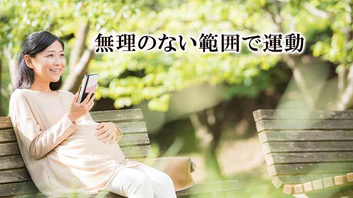 公園のベンチで一休みする妊婦