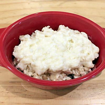 耐熱皿の中に炒めた鶏ひき肉と豆腐を入れ、うえにクリームソースと粉チーズをふりかける@