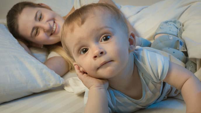 ベッドで横になる母親と元気いっぱいの赤ちゃん
