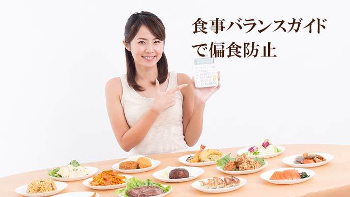 色々な種類の料理が並ぶテーブル前でカロリー計算する女性
