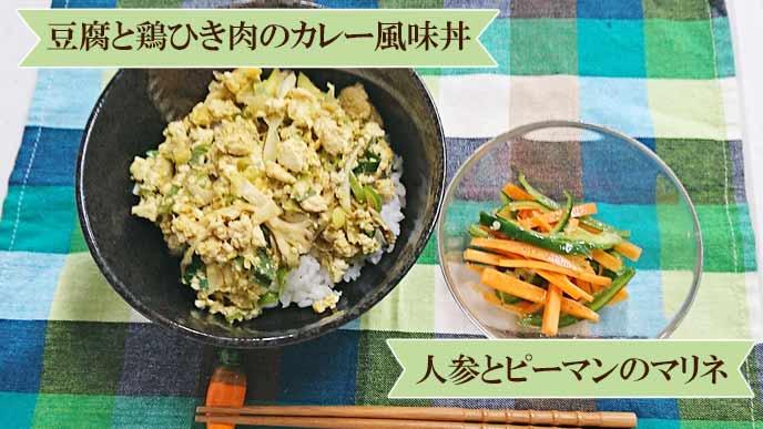 盛り付けられた豆腐と鶏ひき肉のカレー風味丼、人参とピーマンのマリネ