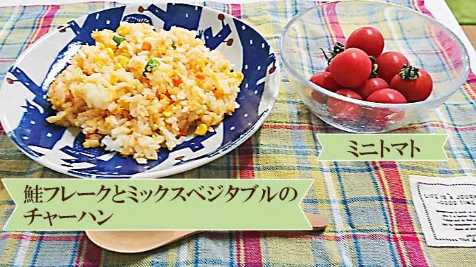 盛り付けられた鮭ミックスベジタブルのチャーハンとミニトマト