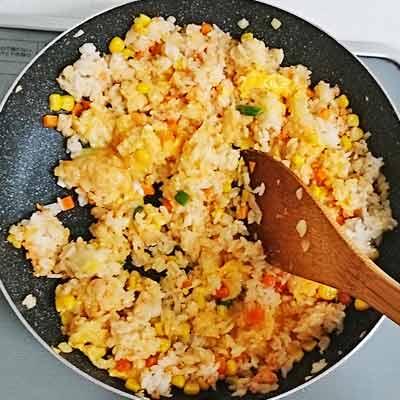 フライパンの中で炒められるミックスベジタブルとご飯と卵