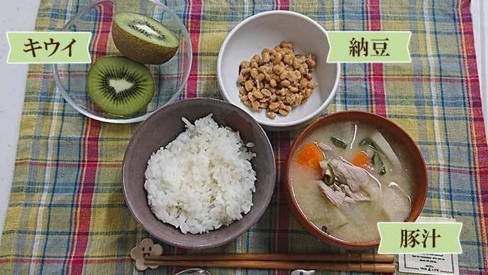盛り付けられた白米と豚汁と納豆とキウイ