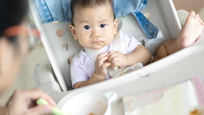 ベビーチェアで食事をとる赤ちゃん