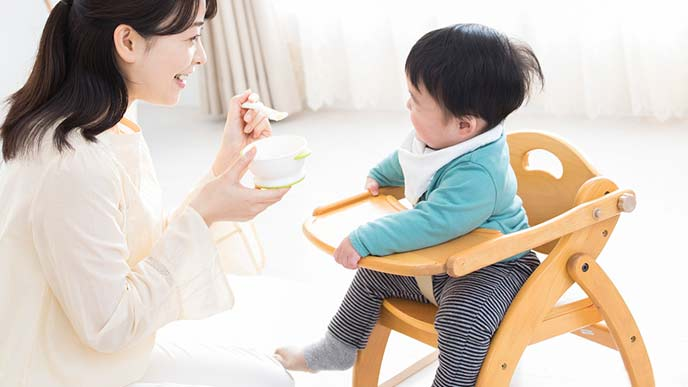 ローチェアに座って離乳食を食べる幼児