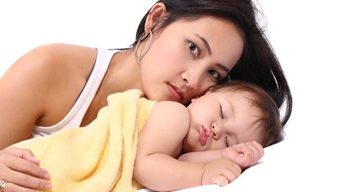 赤ちゃんのお尻を軽くたたいて眠らせる母親