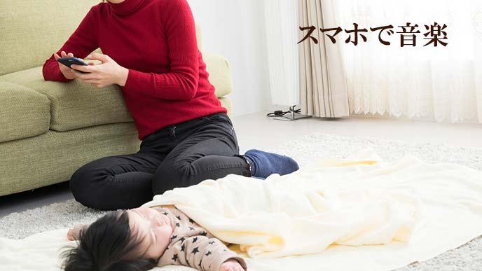 スマホで睡眠アプリの音楽を赤ちゃんに聞かせる母親