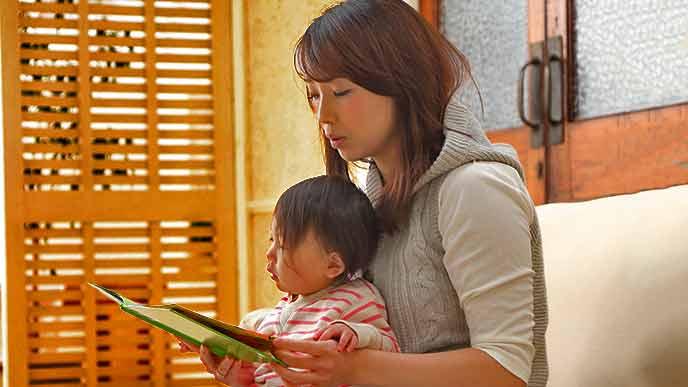赤ちゃんに絵本を読み聞かせる母親