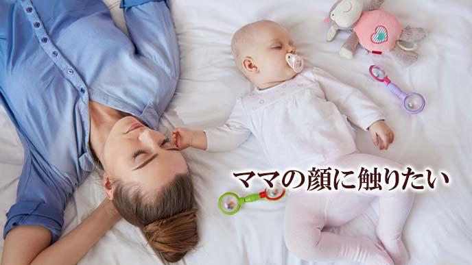 ママの顔に手を付けながら眠る赤ちゃん