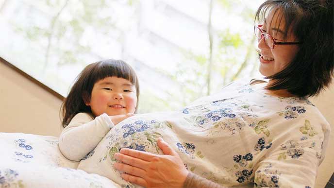 妊娠してる母親のお腹を触る娘