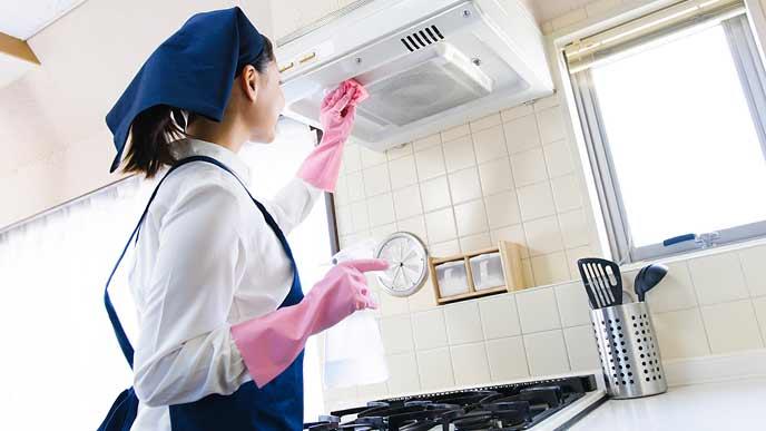 台所のレンジの掃除をする家事代行の女性