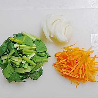 まな板のにある2センチ程度の小松菜、千切りされた人参、スライスされた玉ねぎ