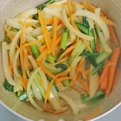 鍋の中で炒められる人参、玉ねぎ、小松菜