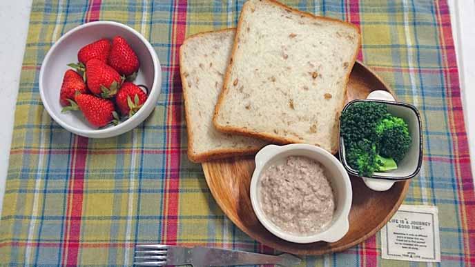 盛り付けられたライ麦パン、ブロッコリー、サバのディップ、いちご