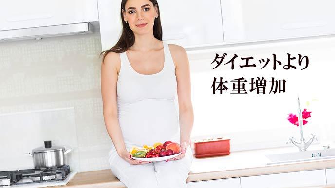 果物を盛った皿を持つ妊婦