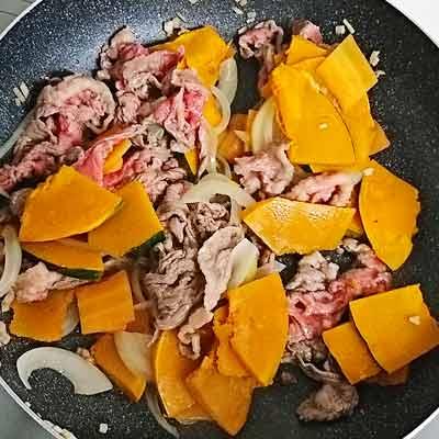 鍋の中で炒められる牛肉とかぼちゃの玉ねぎと人参