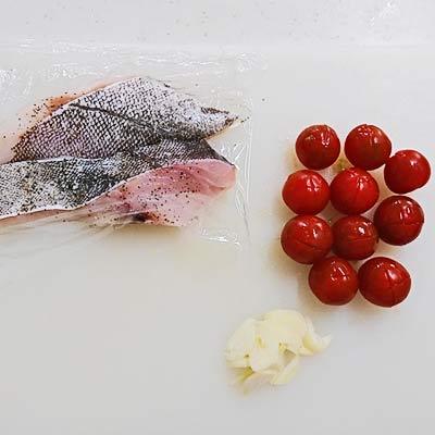 まな板の上にある塩コショウをふられたタラの切り身、ミニトマト、にんにく