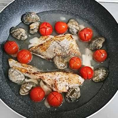 フライパンの中にあるタラ、あさり、トマト