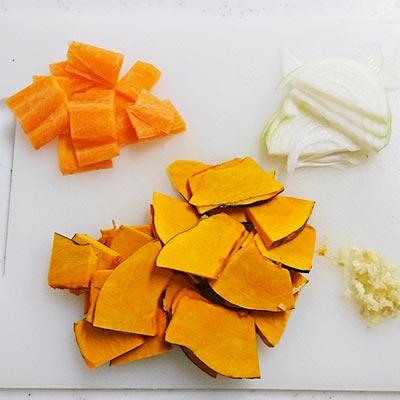 まな板の上にある薄切りのかぼちゃ、短冊切りされたにんじん、スライス玉ねぎ、みじん切りされた生姜