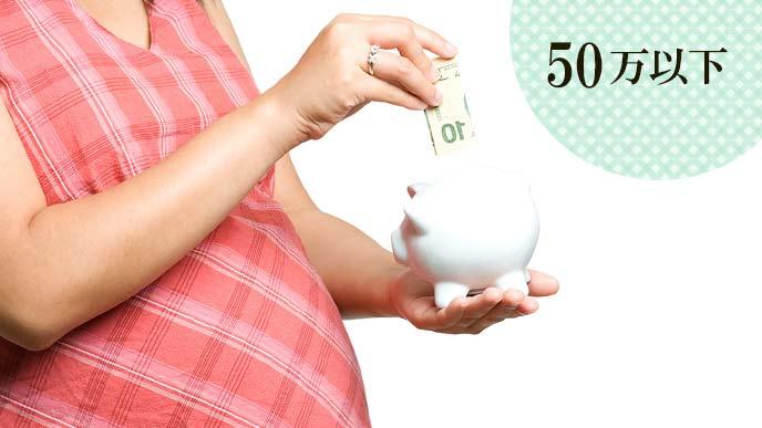 貯金箱にお札を入れる妊婦