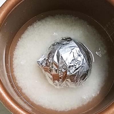 炊飯器の釜の中にセットされたアルミホイルに包まれたかぶ