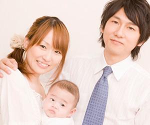 赤ちゃんを抱っこした妻の肩を抱く夫