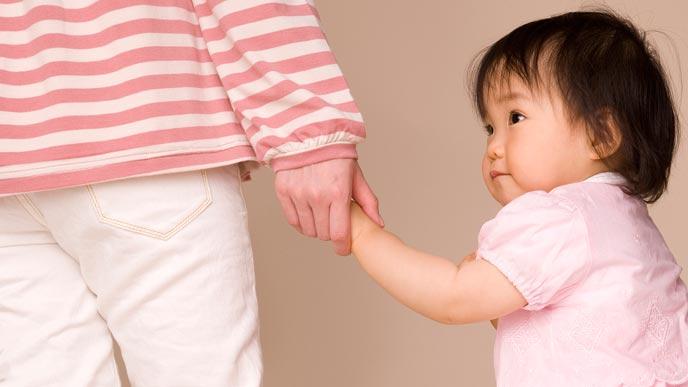 赤ちゃんの手を引いて歩く母親