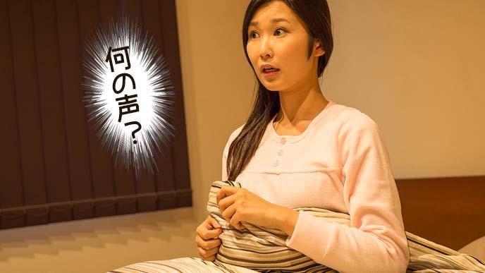 夜中に赤ちゃんの声に驚いて起きる女性