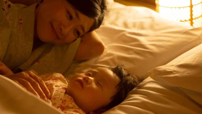 夜赤ちゃんに添い寝しながら見守る母親
