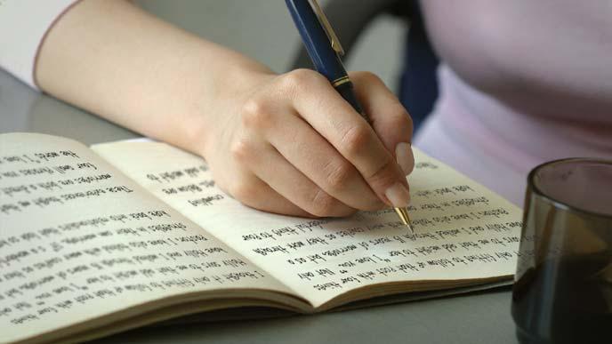 ノートに文章を書いている女性の手元