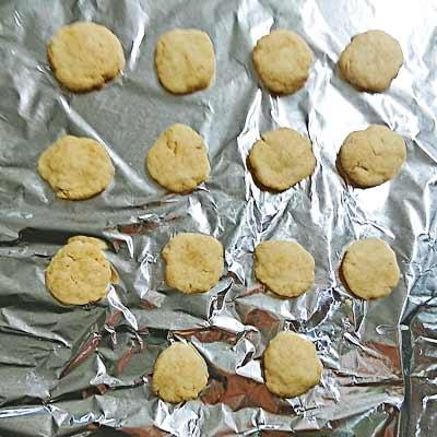 アルミホイルの上に並べられた丸く成型されたきなこクッキーの生地