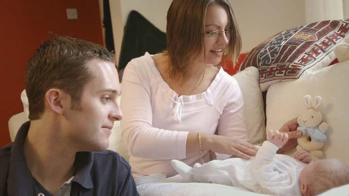 赤ちゃんの面倒を見る女生徒、傍らで見守る男性