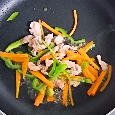 フライパンで炒められる豚もも肉とにんじんとピーマンの千切り