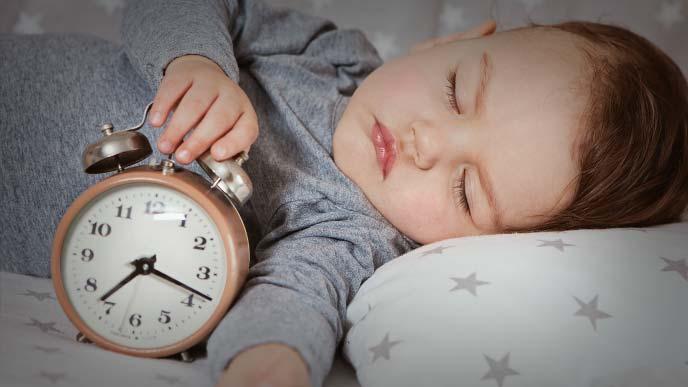 目覚まし時計をつかんだまま寝ている赤ちゃん