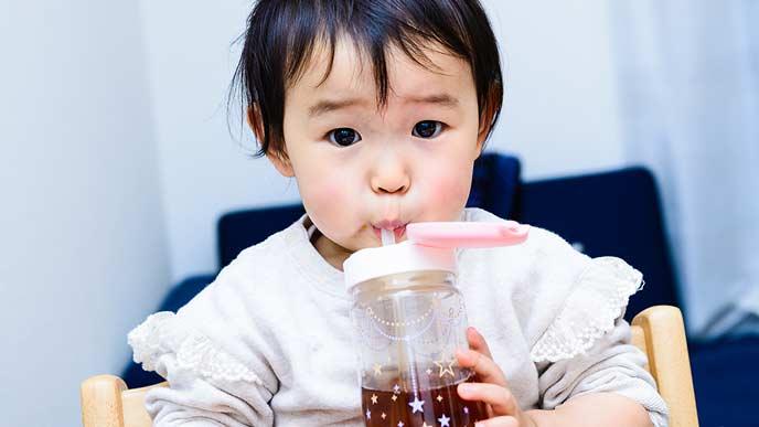 ストローでジュースを飲む赤ちゃん