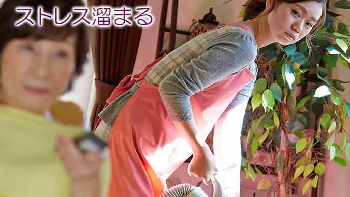 姑の傍で掃除機をかける女性