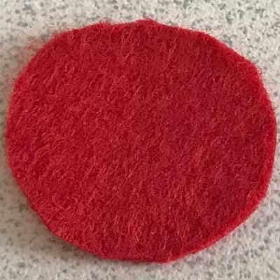 くるみボタンのサイズにあわせて丸くカットされた三枚の赤いフェルト