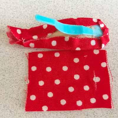 ピンの部分を除き布に包まれたパッチン留めと、切れ目を入れた小さい布