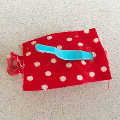 小さい布の切り込みにピンの部分を通したパッチン留め裏側