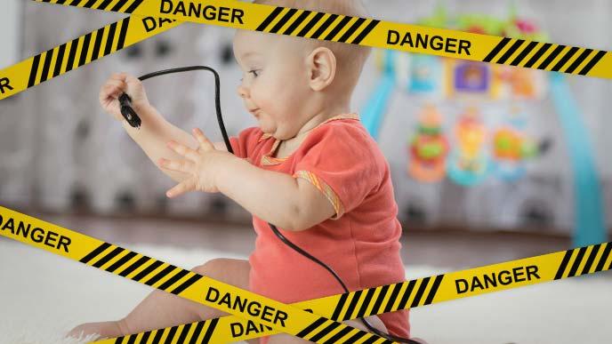 危険:電源コードをいたずらしている赤ちゃん