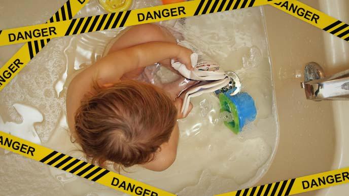 危険:水の少ないバスタブで遊ぶ赤ちゃん