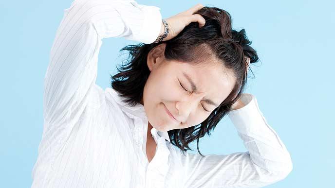 頭を両手でつかんで苦悶の表情の女性